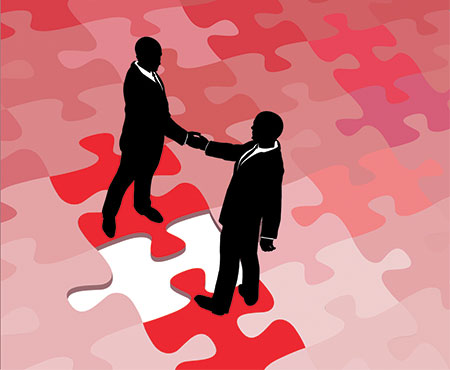 two people shaking hands on puzzle pieces